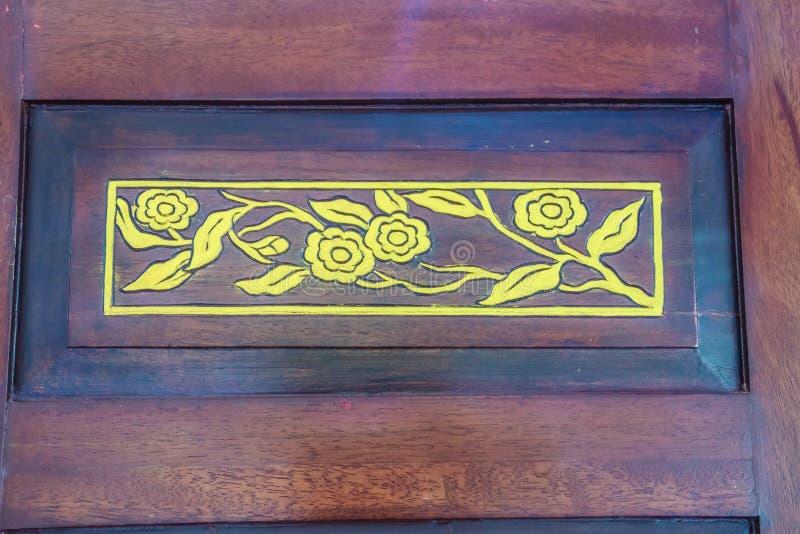 Modello di fiore dorato scolpito nel permesso di legno rosso della porta fotografia stock libera da diritti
