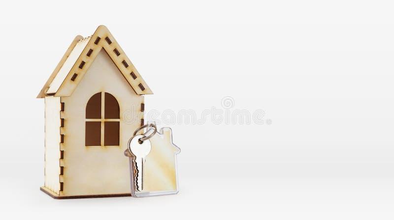 Modello di legno della casa e una chiave su un keychain fotografia stock libera da diritti