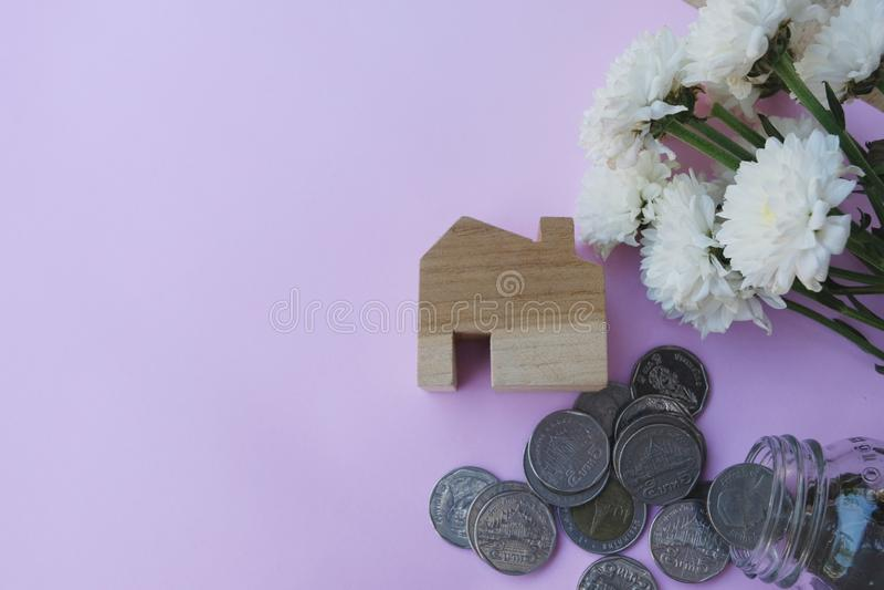 Modello di legno della casa, monete che scorrono fuori dal barattolo di vetro su fondo rosa pastello Finanza della Camera, ipotec immagine stock libera da diritti