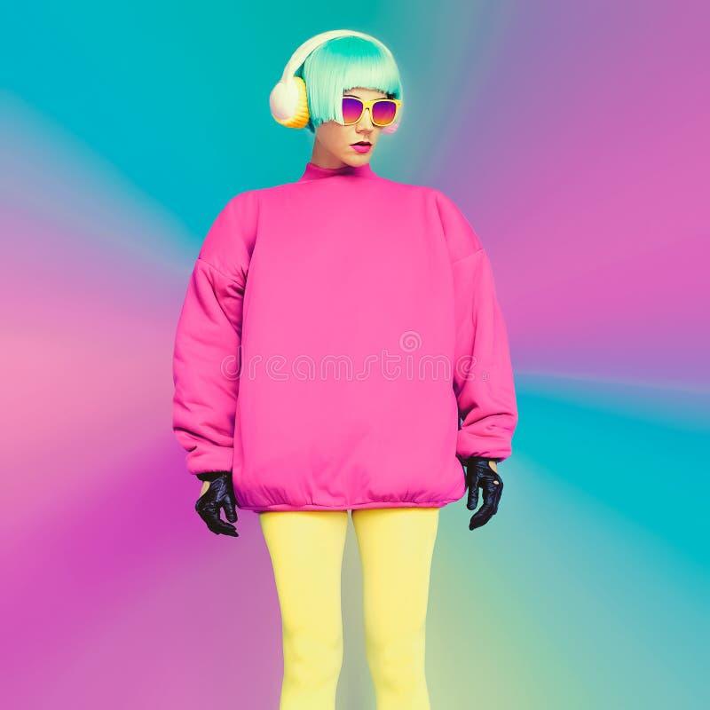 Modello di moda affascinante in vestiti luminosi su un fondo blu l fotografie stock