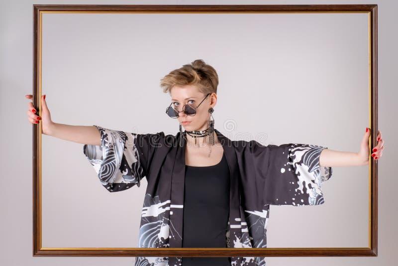 Modello di moda biondo in vestiti alla moda che tengono struttura di legno fotografie stock