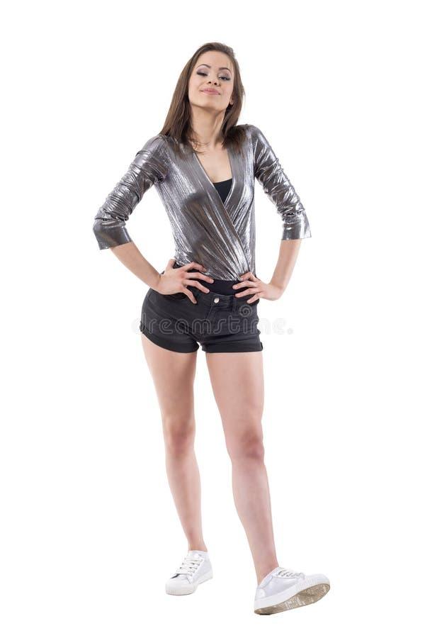Modello di moda castana d'avanguardia della donna di stordimento sicuro che posa con le mani sulle anche immagini stock