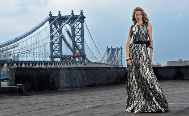 Modello di moda che posa il vestito da sera lungo sexy e d'uso su posizione del tetto fotografia stock libera da diritti