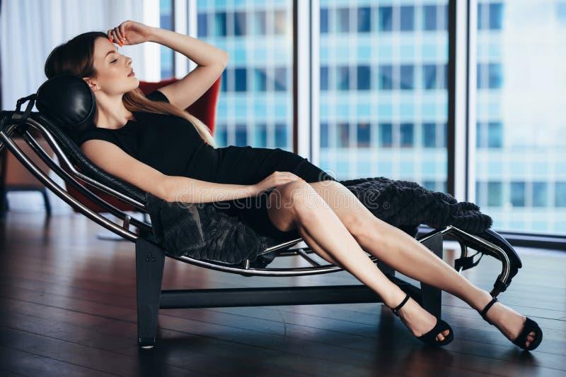 Modello di moda con le gambe lunghe esili che portano vestito da cocktail nero che si trova sulla sedia di salotto in appartament fotografia stock libera da diritti