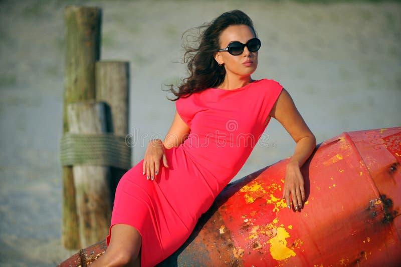 Modello di moda di fascino che posa sulla spiaggia fotografia stock libera da diritti