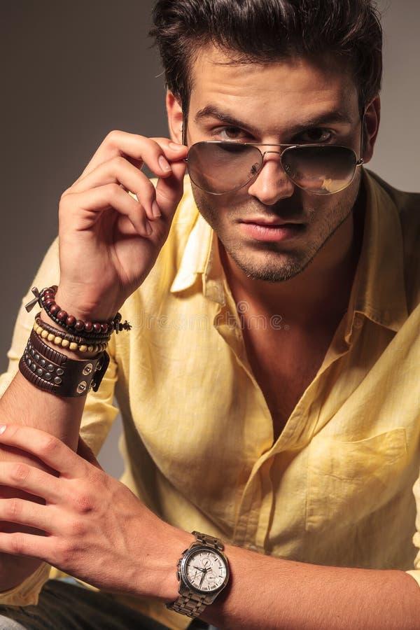 Modello di moda fresco che decolla i suoi occhiali da sole fotografia stock