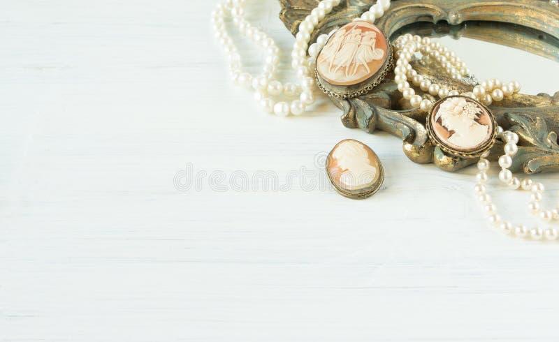 Modello di moda Jewelry Fondo d'annata dei gioielli Bei collana della perla, braccialetto e broochs del cammeo su una vecchia str fotografie stock libere da diritti