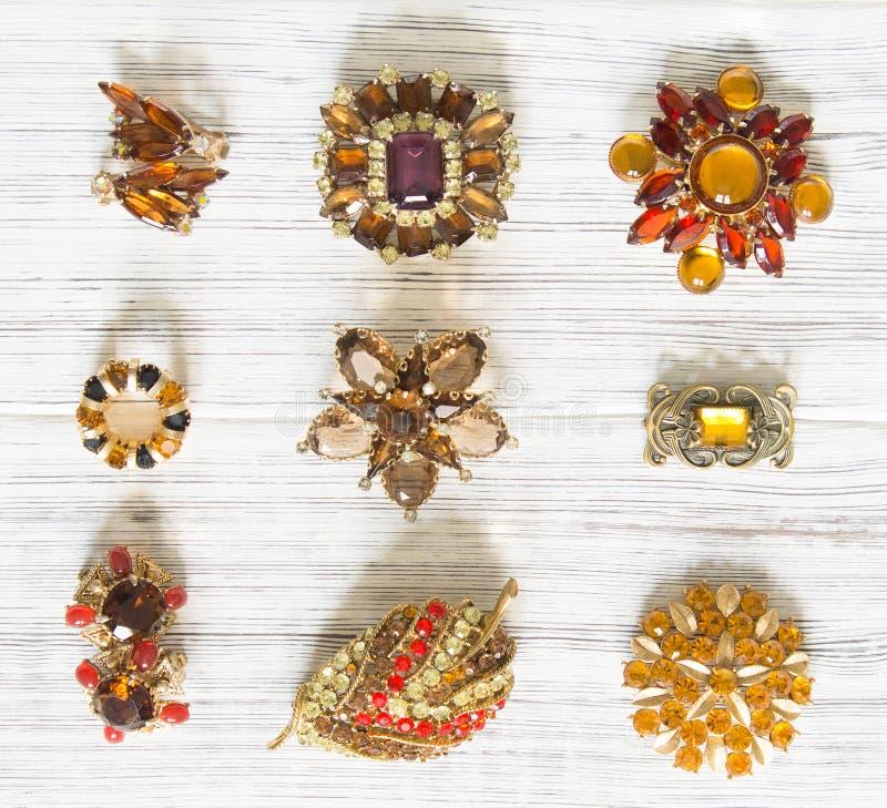 Modello di moda Jewelry Fondo d'annata dei gioielli Bei fibula ed orecchini luminosi del cristallo di rocca su legno bianco Dispo immagini stock