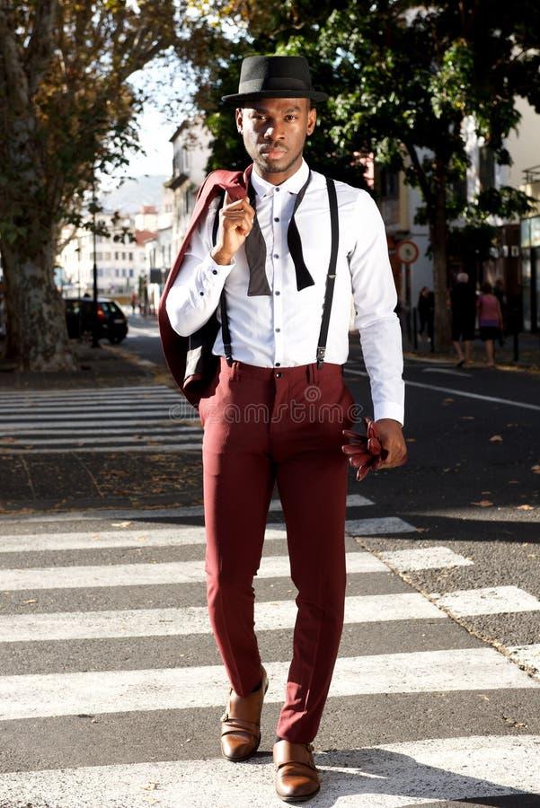 Modello di moda maschio nero bello dell'ente completo che cammina nella città con il vestito immagini stock