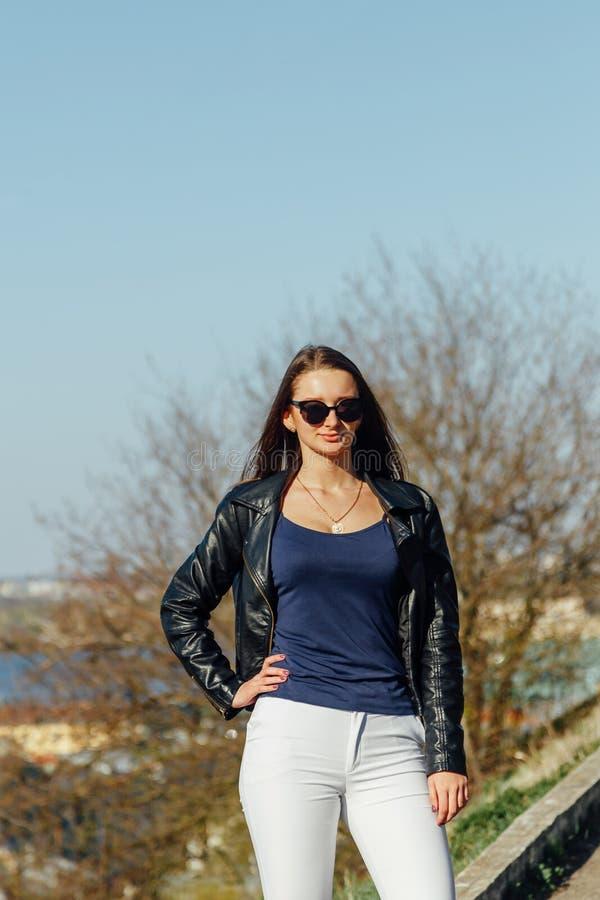 Modello di moda in occhiali da sole e nella posa nera del bomber all'aperto immagine stock