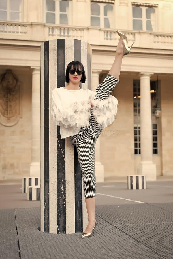 Modello di moda in occhiali da sole sul quadrato Modo e moda Concetto di sport e di yoga Donna sensuale con capelli castana fotografia stock libera da diritti
