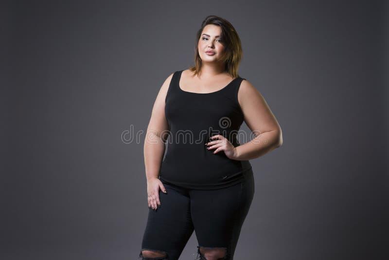 Modello di moda più in abbigliamento casual, donna grassa su fondo grigio, ente femminile di peso eccessivo di dimensione fotografia stock