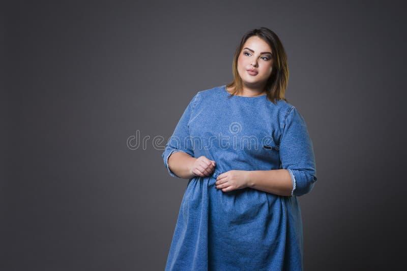 Modello di moda più in abbigliamento casual, donna grassa su fondo grigio, ente femminile di peso eccessivo di dimensione immagini stock