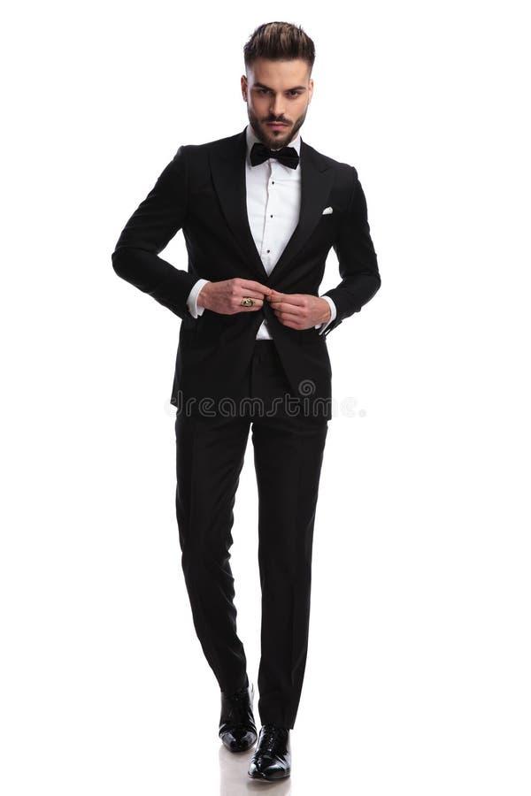 Modello di moda serio che abbottona il suo smoking mentre camminando fotografia stock