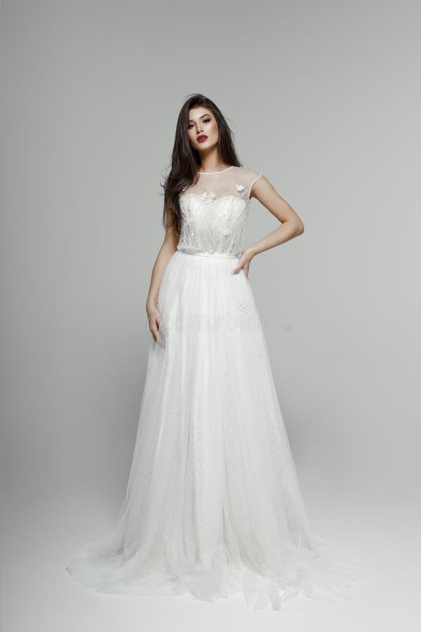 Modello di moda in vestito da sposa Giovane sposa sensuale in vestito bianco Esaminando macchina fotografica, isolata su un fondo immagini stock libere da diritti