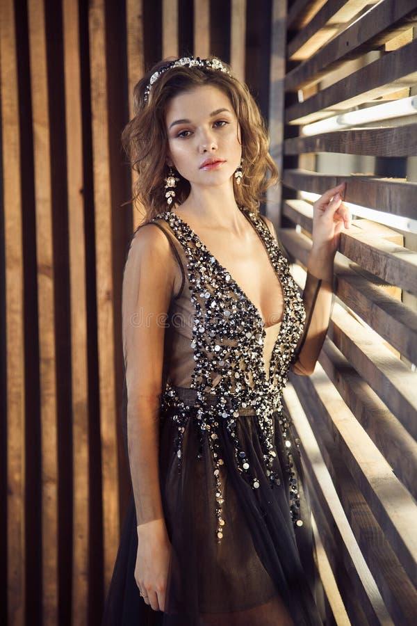 Modello di moda in vestito nero lungo con la corona immagini stock libere da diritti