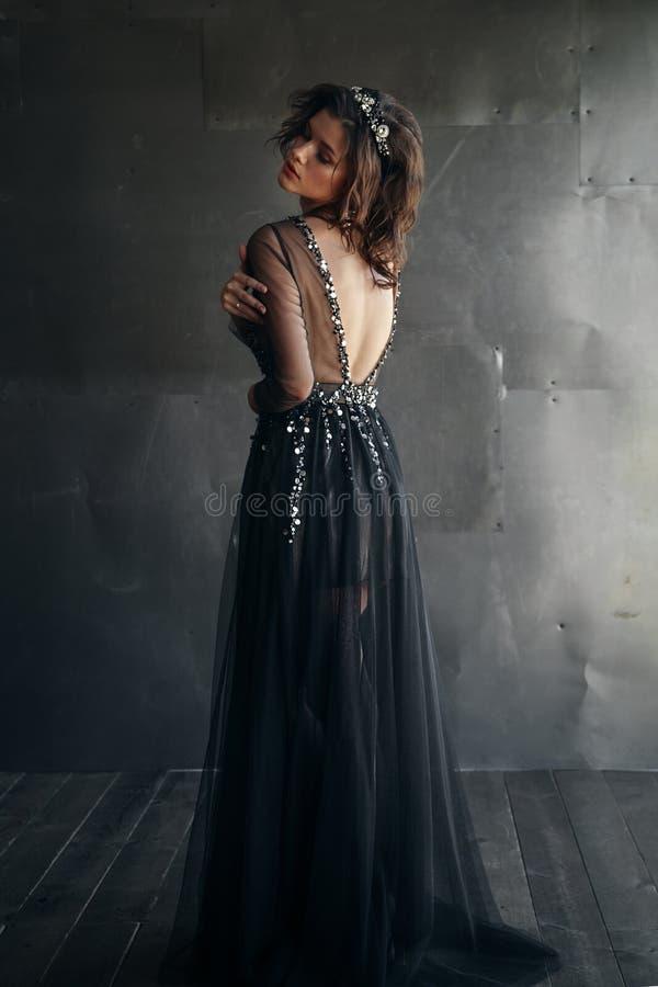 Modello di moda in vestito nero lungo con la corona fotografia stock