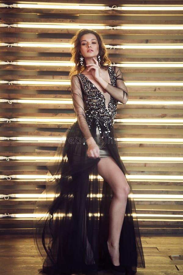 Modello di moda in vestito nero lungo con la corona fotografie stock