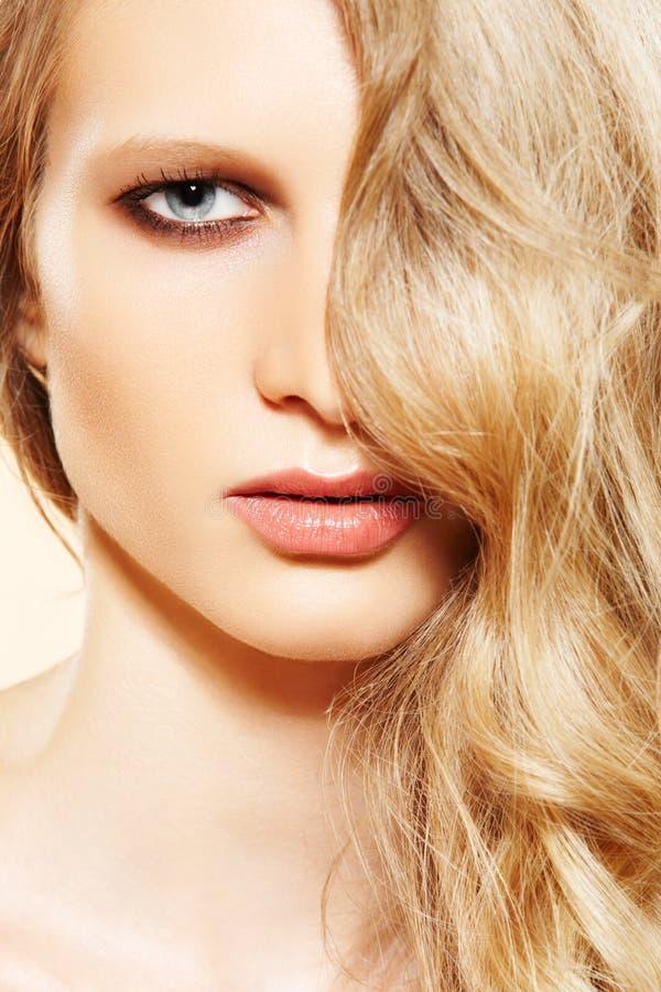 Modello di modo. Bei capelli biondi lunghi, trucco fotografia stock
