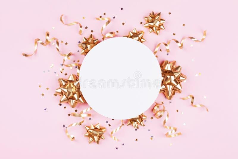 Modello di modo con i coriandoli dorati degli archi, della serpentina e della stella sulla vista pastello rosa del piano d'appogg fotografia stock libera da diritti