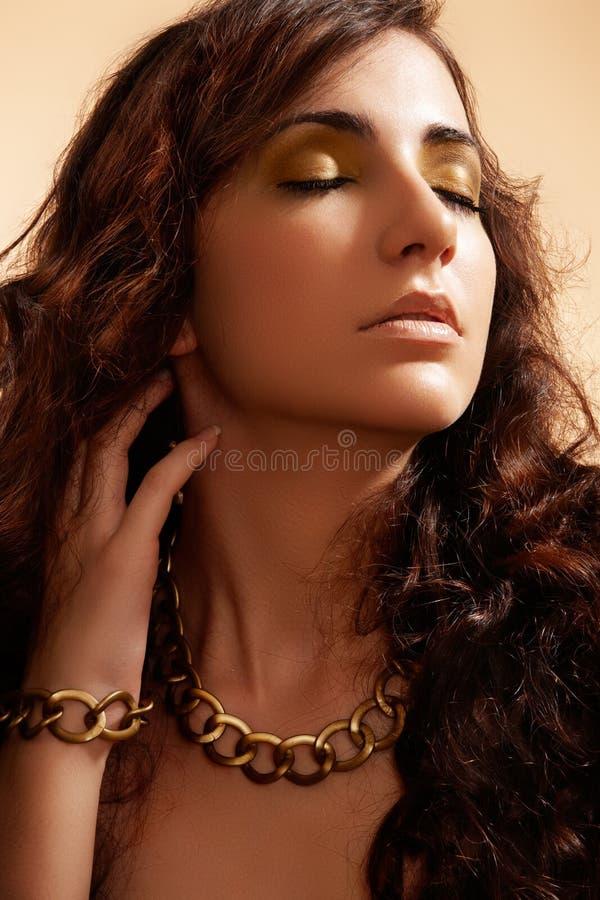 Modello di modo di lusso con l'accessorio dell'oro di fascino fotografia stock libera da diritti
