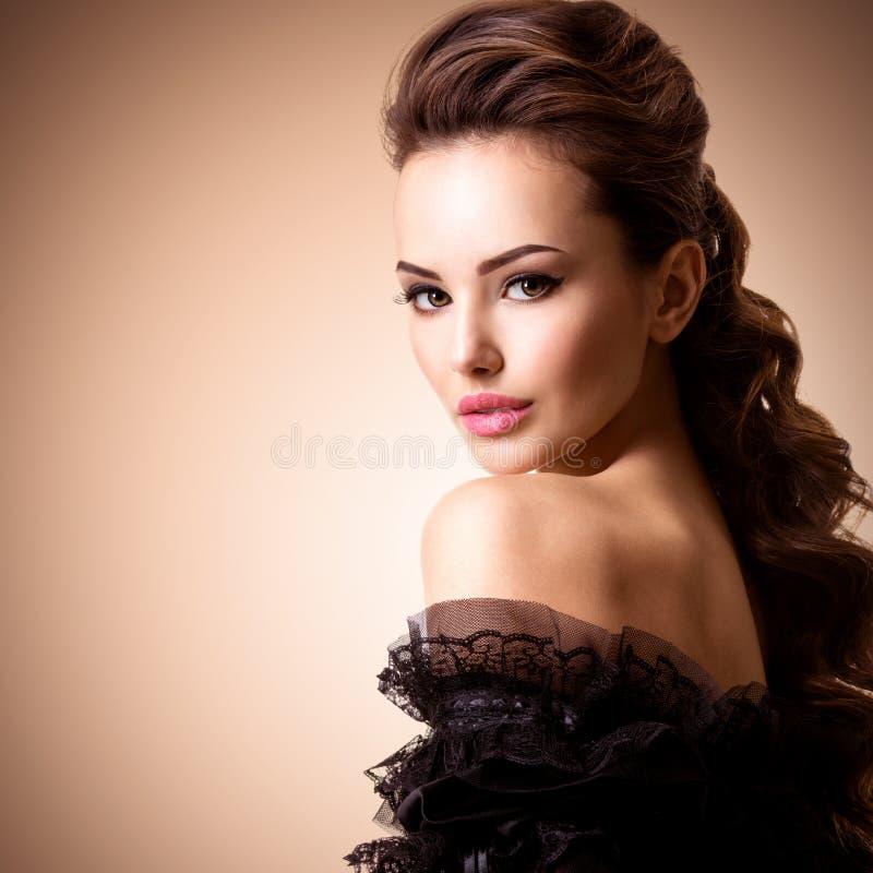 Modello di modo in vestito dorato Modello con i capelli ricci lunghi Acconciatura creativa immagini stock