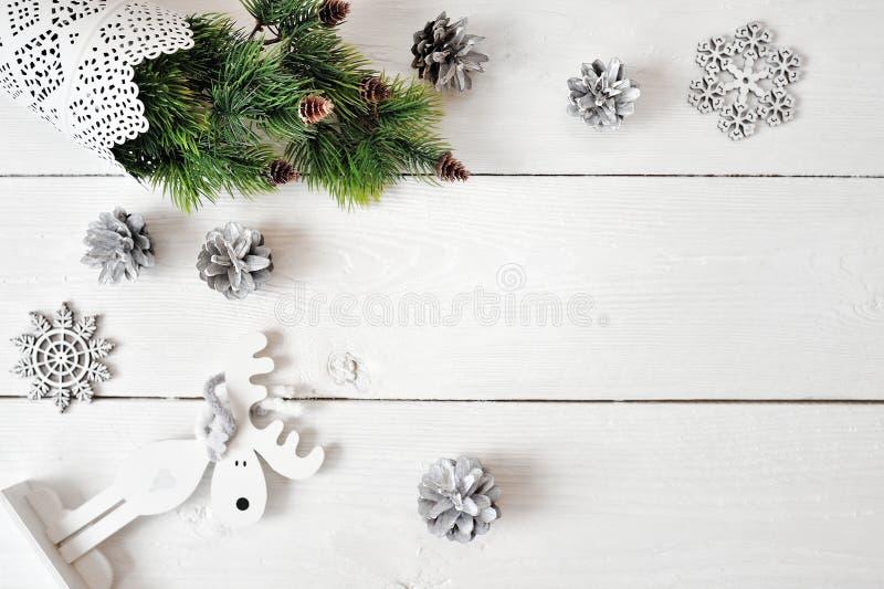 Modello di Natale su un fondo di legno bianco con i fiocchi di neve, un cervo e un albero di Natale Disposizione piana, vista sup fotografia stock