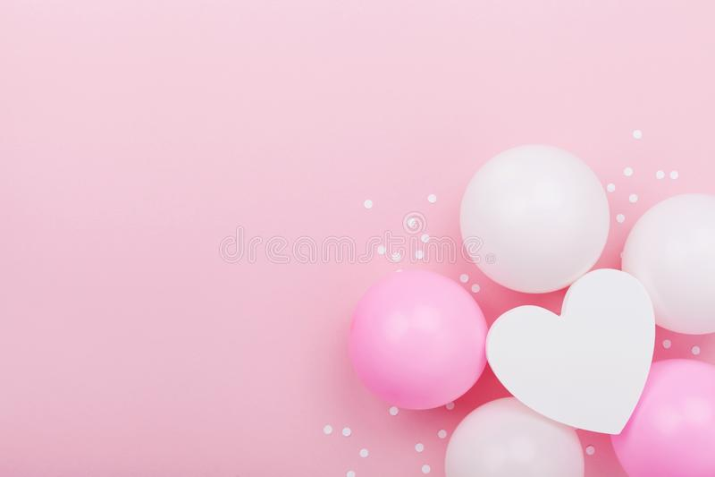 Modello di nozze o di compleanno con forma bianca del cuore, coriandoli ed i palloni pastelli sulla tavola rosa da sopra Composiz fotografia stock libera da diritti