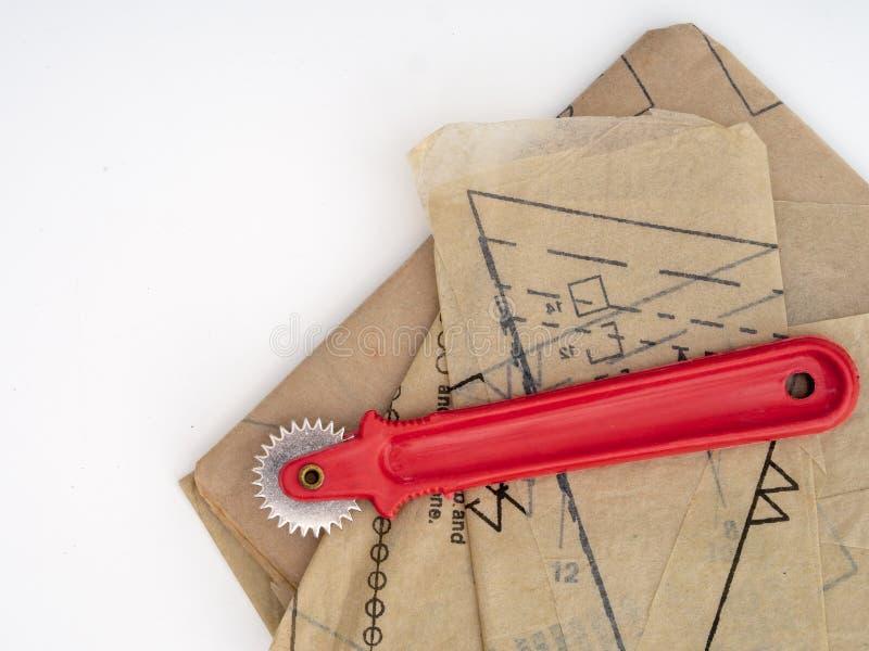 Modello di rintracciamento di sartoria della carta e della ruota, elementi di cucito della casa isolati su bianco fotografie stock libere da diritti