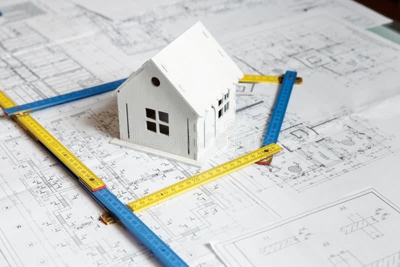 Modello di una casa sopra i modelli e gli strumenti dell'architetto immagine stock libera da diritti