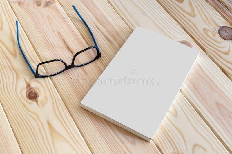 Modello di vetro e del libro su fondo di legno fotografia stock libera da diritti