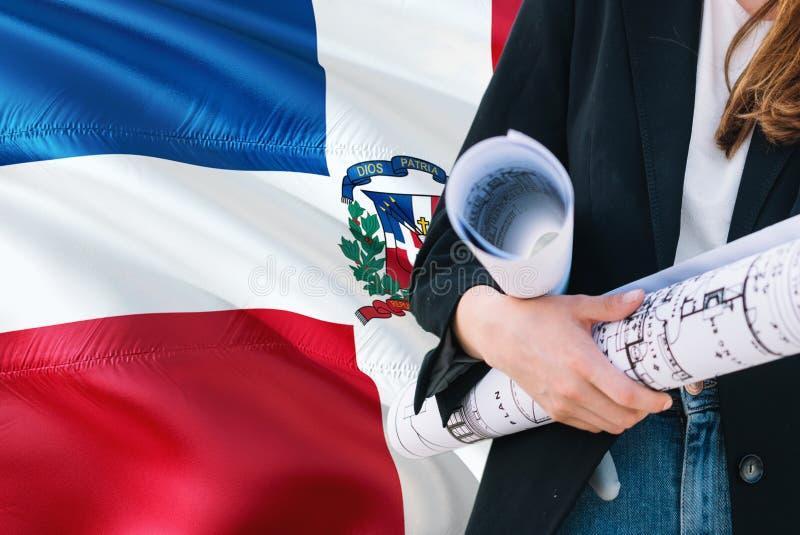 Modello domenicano della tenuta della donna dell'architetto contro il fondo d'ondeggiamento della bandiera della Repubblica domin fotografia stock libera da diritti
