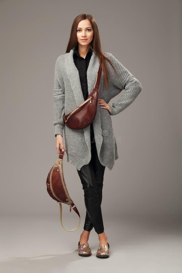 Modello elegante in cardigan tessuto grigio con due pacchetti di fanny di cuoio immagine stock libera da diritti