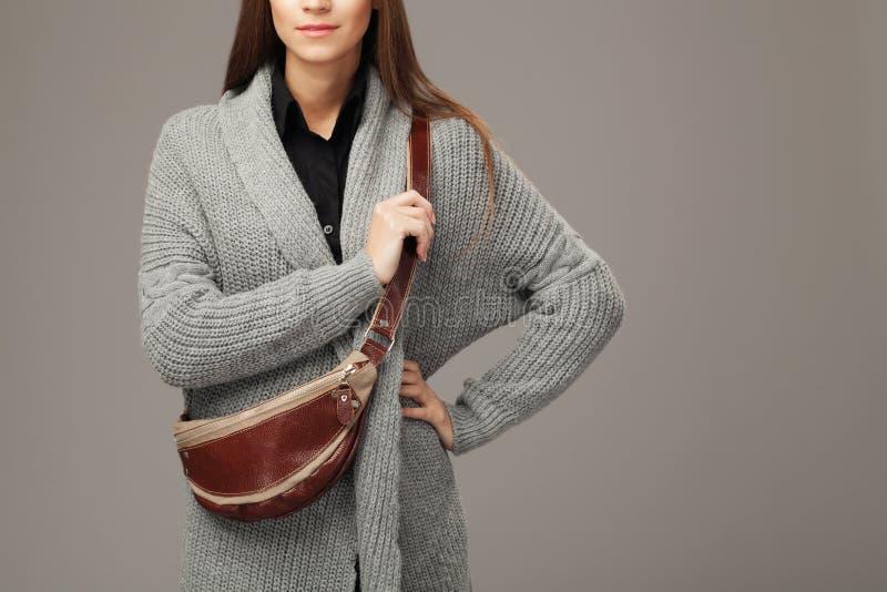 Modello elegante in cardigan tessuto grigio con un pacchetto di fanny di cuoio fotografia stock libera da diritti