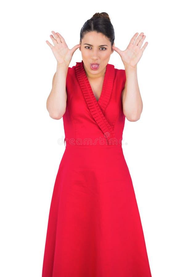 Modello elegante in vestito rosso che fa i fronti immagini stock