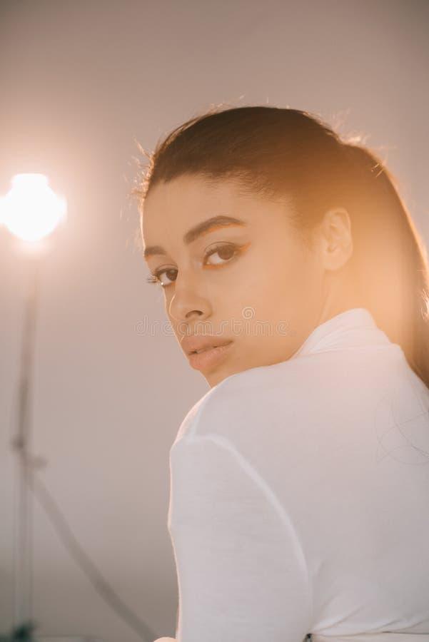 modello femminile afroamericano grazioso che esamina macchina fotografica e che posa nello studio fotografia stock libera da diritti