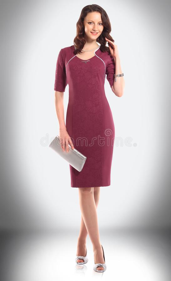 Modello femminile attraente in un vestito elegante da Borgogna fotografia stock