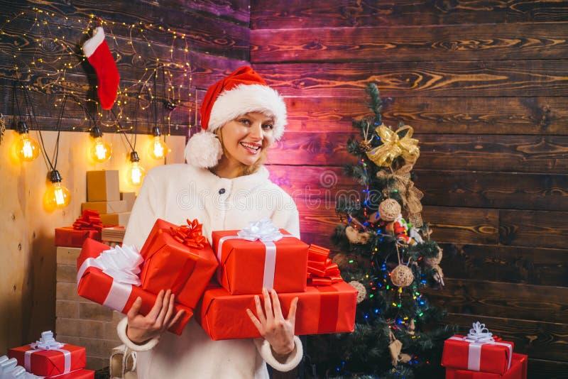 Modello femminile biondo vestito in un cappello di Santa Claus Giovane donna sveglia con il cappello di Santa euphoria Ritratto d fotografia stock libera da diritti