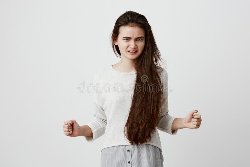 Modello femminile castana feroce ed arrabbiato in abbigliamento casual che tiene i pugni nell'irritazione, fronte aggrottante le  fotografie stock libere da diritti