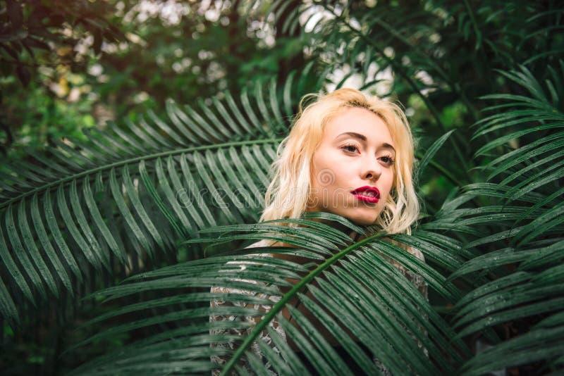 Modello femminile caucasico sensuale vago in foglie verdi della palma fotografia stock