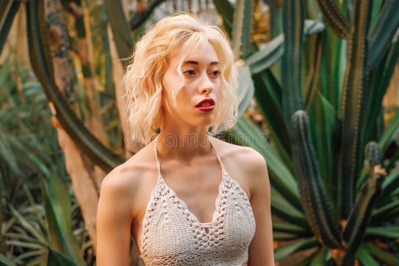 Modello femminile caucasico vago fra i grandi cactus immagini stock