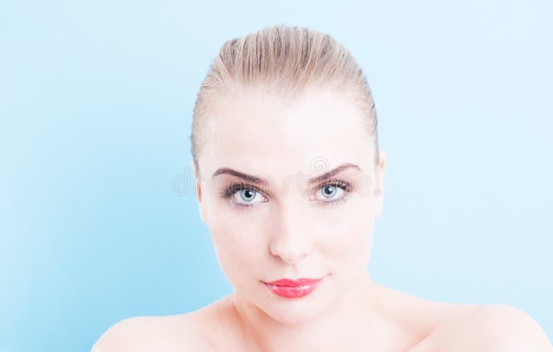 Modello femminile del bello fronte sul fondo del turchese o del blu fotografia stock