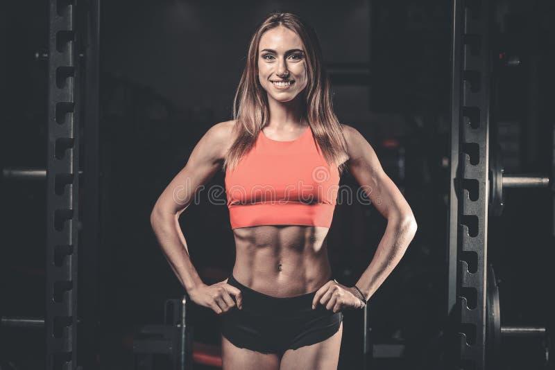 Modello femminile di forma fisica sexy caucasica nella fine della palestra sull'ABS fotografia stock