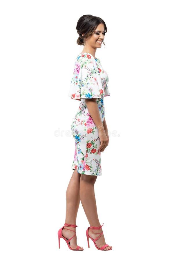 Modello femminile di modo femminile timido elegante in vestito floreale che sorride e che guarda giù fotografia stock