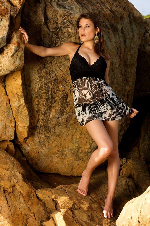 Modello femminile grazioso che si leva in piedi sulle rocce fotografia stock libera da diritti