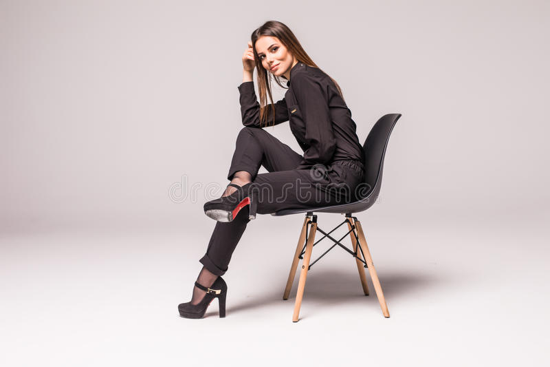 Modello femminile sexy timido attraente caucasico impressionante con capelli castana che posano sulla tavola in studio, vestito c fotografia stock libera da diritti