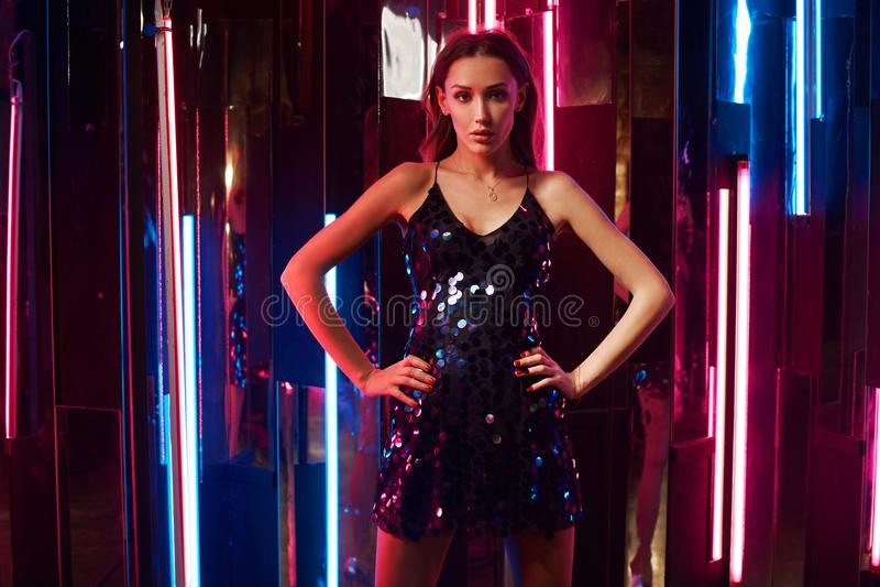 Modello femminile in vestito brillante nero da cami che si siede sul grande cubo e immagine stock