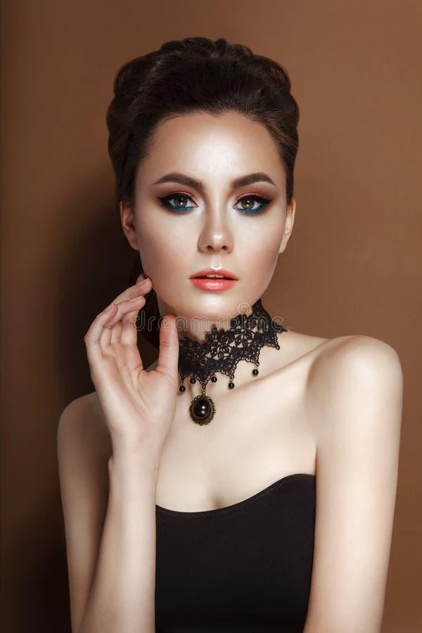 Modello Girl di bellezza di alta moda con il corsetto del nero dei capelli e la collana castana raccolti del pizzo fotografie stock libere da diritti
