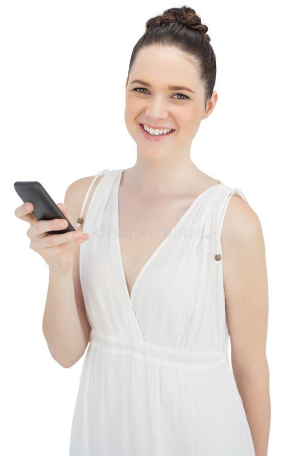 Modello grazioso allegro in vestito bianco che invia messaggio di testo fotografia stock libera da diritti