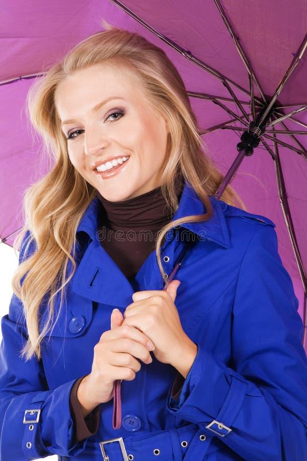 Modello grazioso in cappotto blu che tiene un ombrello immagine stock